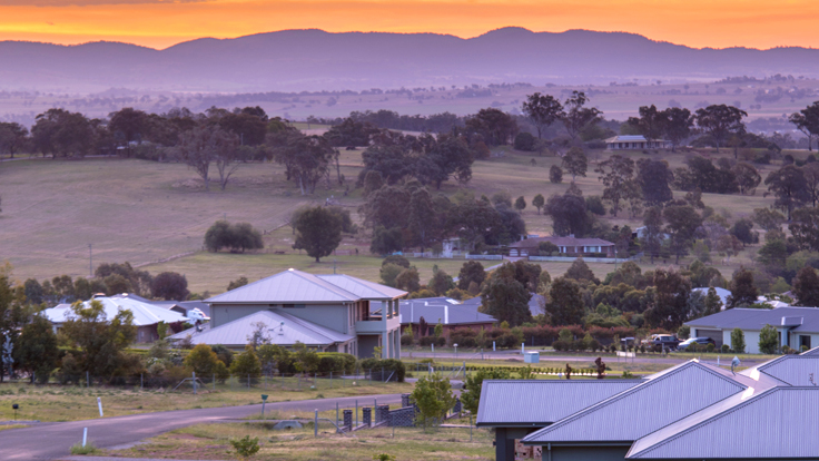 Image of rural flood prone land in regional NSW - a mountain range in the sunset and a plane with rural housing